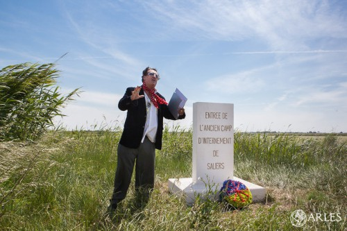 Jérôme Bonin raconte l'histoire du camp, devant la borne qui indique l'emplacement de l'entrée. photo O. Quérette/ektadoc/ville d'Arles.