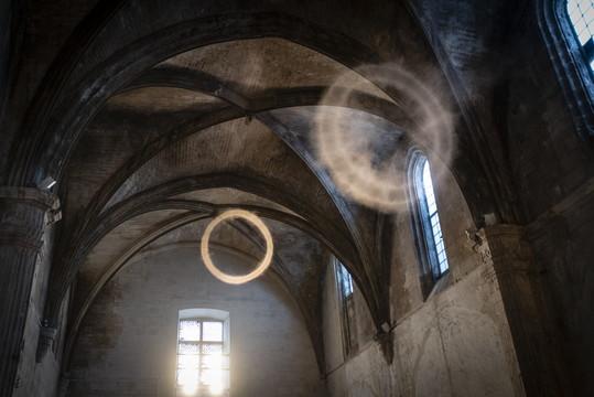 Ce n'est pas un mirage, encore moins un tour de magie mais l'oeuvre bien réelle de l'artiste Guillaume Cousin, à découvrir à l'église des Trinitaires (rue de la République) dans le cadre d'ON. Grâce à une étrange machine, des anneaux de fumée voyagent sous les voûtes de l'édifice... Toutes les installations d'ON sont à voir jusqu'à la fin du mois. Programme sur https://on-arles.com/ photo P. Praliaud/ville d'Arles.